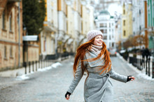 Attractive Smiling Red Haired Woman Wearing Stylish Winter Outfit Walking In City, Spinning Around. Empty Space