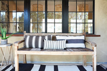 Bench With Black And White Pillows On Front Porch Of Home