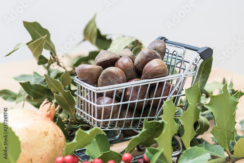 In de dag Assortiment Fall and winter seasonal background, copy space image with laurel leaves and a shopping trolley full of chestnuts