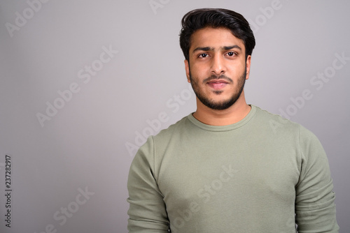 Fotografia  Portrait of young handsome Indian man against gray background