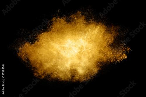 Fototapeta Golden color Explosion. Glitter dust particles isolated on black background obraz