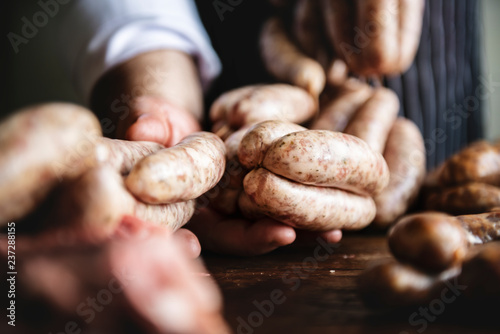 Butcher with smoked sausages on a string