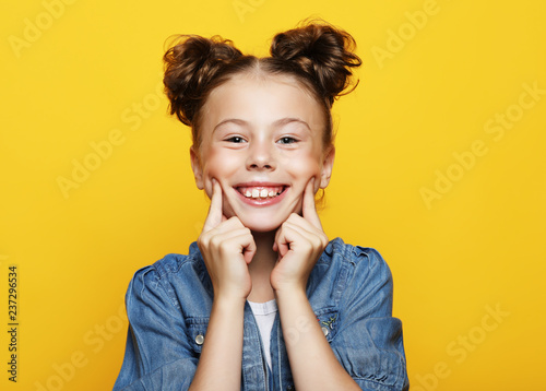 Portrait of cheerful smiling little girl on yellow background