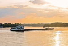 Tugboat Pushes Barge With Sand In The River At Sunset
