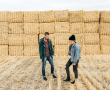 Couple In Front Of Fall Hay Stack Scene As Background