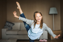 Cheeky Little Girl Practicing Gymnastics In Her Living Room.