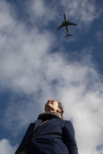 View Of A Woman From Below With Lots Of Sky And An Aeroplane.