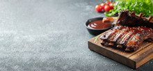 Closeup Of Pork Ribs Grilled With BBQ Sauce And Caramelized In Honey. Tasty Snack To Beer On A Wooden Board For Filing On Dark Concrete Background. With Copy Space