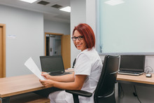 Cheerful Nurse Working At The Hospital Office
