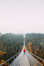 Man Walking On A Long Bridge In Nature