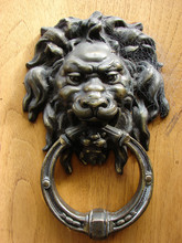 Old Metal Door Handle In The Form Of A Lion's Head Covered In Cobwebs Close Up