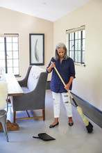 Mature Woman Cleaning At Home, Sweeping The Floor With A Broom