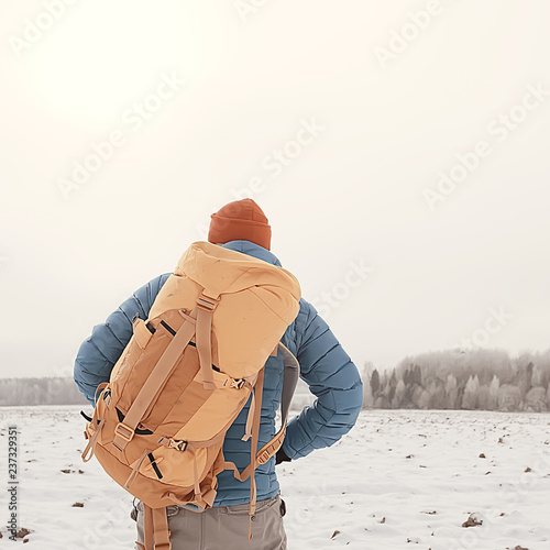 Staande foto Hoogte schaal back view of tourist with backpack hiking in winter in Norway / one man carrying backpack in a Norwegian winter landscape.