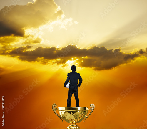 Photo  Business man stand on gold trophy face against sun light and ray through cloud,