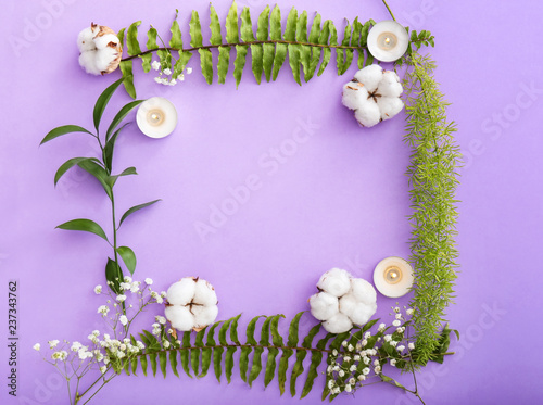 Frame made of burning candles, cotton flowers and tropical