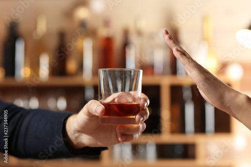 Cuadros en Lienzo  Man with glass of whiskey and woman refusing to drink in bar