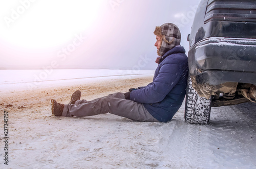 Photo sur Toile Autruche Angry young man waiting for help, sitting near the broken car on the side of the road in the winter in the woods