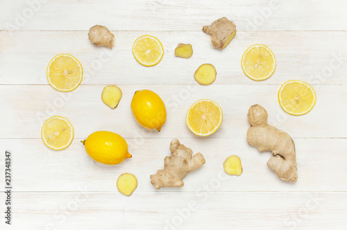 Fresh ginger root and lemon on white wooden background. Flat lay, top view, copy space. Minimalistic style, seasoning, spice, ingredient for tea. Concept healthy food, medicine, improving immunity