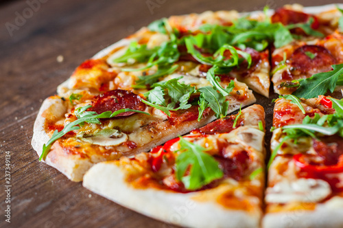 Poster Pays d Europe Pizza with Mozzarella cheese, mushrooms, pepperoni, tomato sauce, salami, pepper, Spices and Fresh arugula. Italian pizza on wooden table background