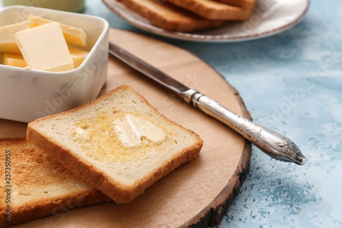 Tasty toasted bread with butter on wooden board Canvas Print