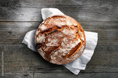 Foto Rustikales Brot auf weißem Tuch mit dunklem Holzuntergrund