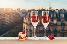 Paris Luxury Lifestyle. Pink Champagne In Two Glasses, Traditional French Cake With Strawberries On A Balcony On The Sunset