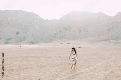 5346eea40d Young indian woman in white long dress walking in the desert with the  mountains on background