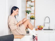 Young Woman With Tangerine Sitting On Kitchen