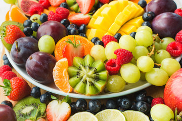 Assorted fruits and berries platter, strawberries blueberries, mango orange, apple, grapes, kiwis background, selective focus