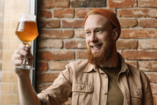 Portrait Of Young Bearded Hipster Man With Happy Emotional Face Holding Glass With Craft Beer, Checking Quality Of Alcohol, Testing Beer And Smiling In Loft Brewery. Successful Small Business Concept