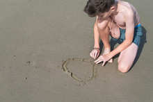 Boy In The Swimming Trunks Draws Shape Of Heart On The Sand On The Beach .  Concept