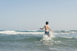 Boy Jumping In Sea Waves with Water Splashes. Concept of summer vacation