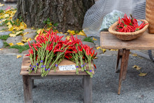 """Bunches Of Fresh Japanese Red Chili With Its Long Green Stem And Vivid Red Color Are Put On Sale At A Japanese Morning Market With A Sign Translated As: """"150 JPY Per Bunch"""""""