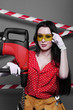 Brunette in red shirt and yellow construction glasses holding a huge industrial drill on a gray background. Construction concept