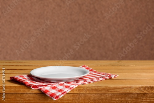 White circle Plate on napkin on wooden table
