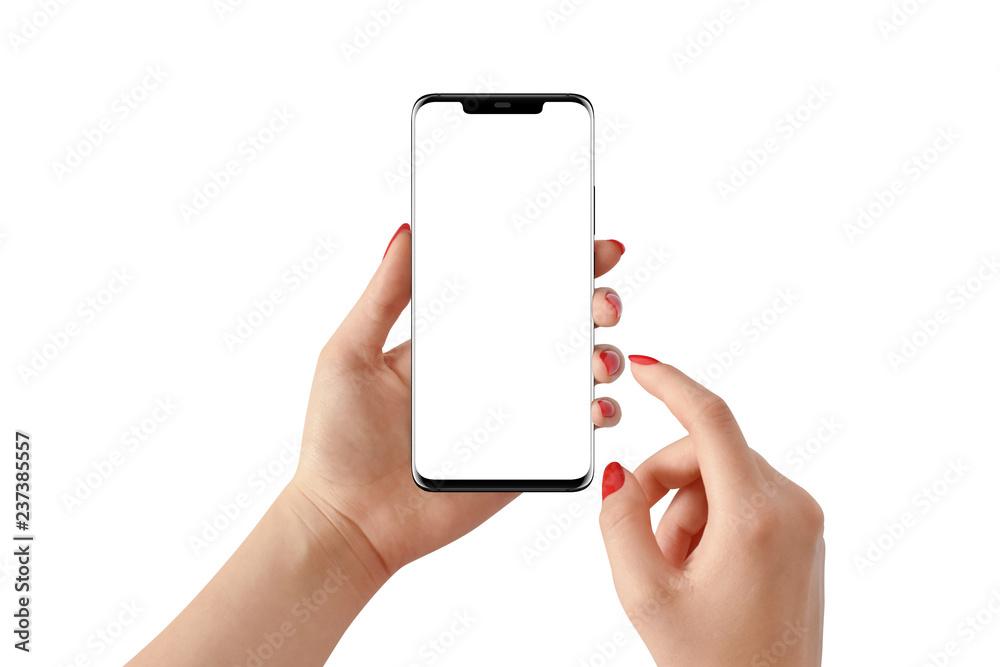 Fototapeta Female hand holding modern black phone in vertical position with empty screen on white background. Mockup