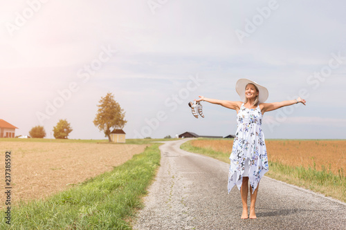 Mature woman standing on remote country lane in summer with outstretched arms