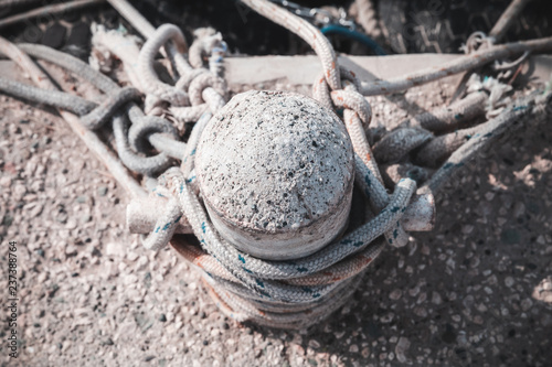 Fotografía  Old bollard with ropes stands on concrete pier, top view