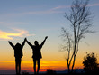 Silhouette of happy two girls standing with raised hands on the mountain at the sunset or sunrise time.