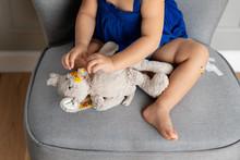 Toddler Putting Plaster On Plush Toy
