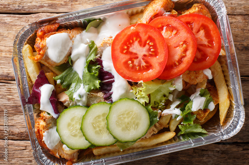 Recipe Dutch fast food kapsalon of french fries, chicken, fresh salad, cheese and sauce close-up. Horizontal top view