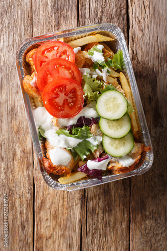 Traditional Dutch fast food kapsalon of french fries, chicken, fresh salad and sauce close-up. Vertical top view