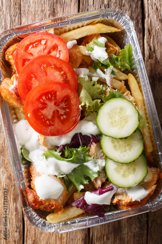 Recipe Dutch fast food kapsalon of french fries, chicken, fresh salad, cheese and sauce close-up. Vertical top view