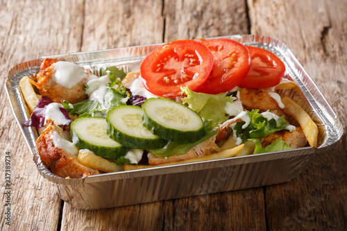 Assortiment Takeaway Dutch kapsalon from french fries, chicken, fresh salad, cheese and sauce in a close-up foil tray. horizontal