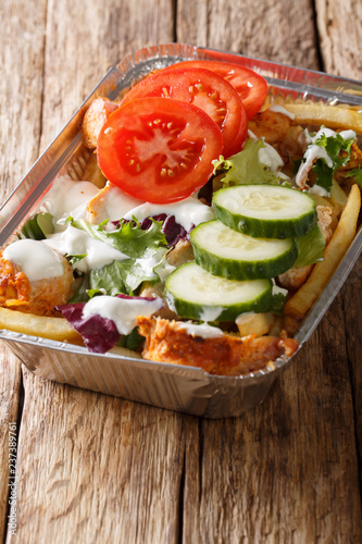 Kapsalon is a Dutch food item consisting of fries, topped with döner or shawarma meat and grilled with a layer of Gouda cheese and fresh vegetables closeup. vertical