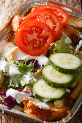 Dutch fast food kapsalon of french fries, chicken, fresh salad and sauce close-up in a foil tray. vertical