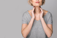Female Checking Thyroid Gland By Herself. Close Up Of Woman In White T- Shirt Touching Neck With Red Spot. Thyroid Disorder Includes Goiter, Hyperthyroid, Hypothyroid, Tumor Or Cancer Health Care.