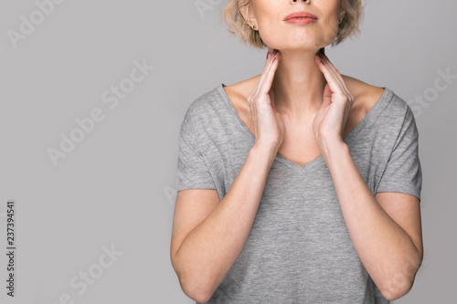 Canvas Print Female checking thyroid gland by herself