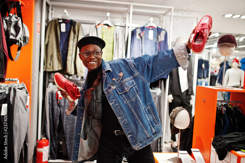 Cuadros en Lienzo  Stylish casual african american man at jeans jacket and black beret at clothes store holding new red sneakers at hands