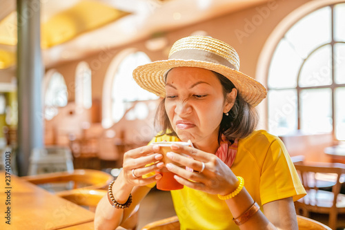 Photo Young woman drinking coffee or tea from paper cup in cafe